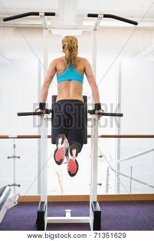 Rear view of a young fit woman doing crossfit fitness workout in gym
