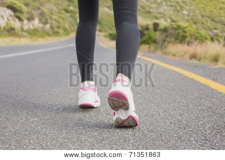 Rear view low section of fit young woman running on the open road