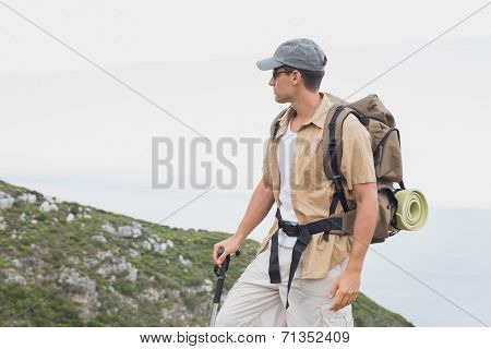 Side view of a hiking man walking on mountain terrain