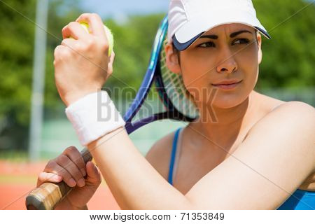Pretty tennis player sitting on court on a sunny day