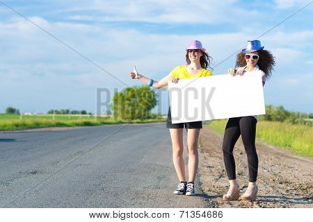 Two young women stand with a blank banner