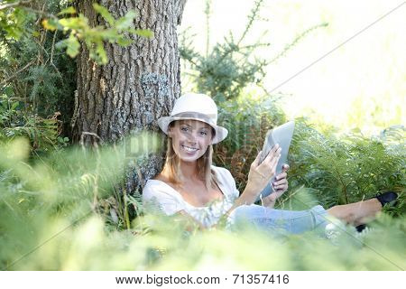 Woman in countryside reading novel on tablet