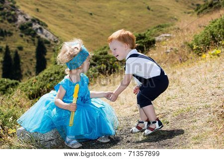 Baby Boy And Adorable Child Girl On Grass. Summer Green Nature Background. The Concept Of Childhood