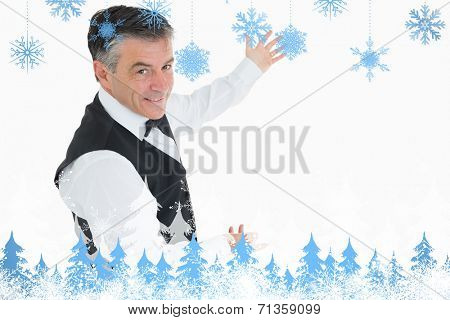 Welldressed man showing us something against snowflakes and fir trees