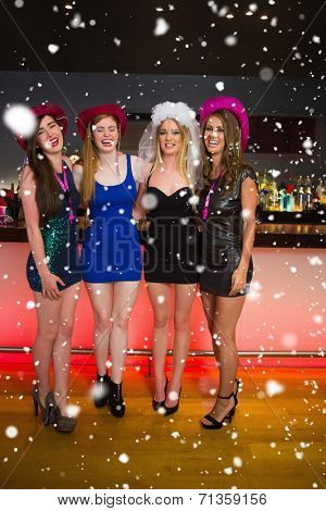 Laughing friends having a hen party at the bar against snow falling