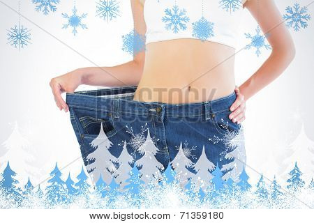 Close up of confident slender blonde wearing too big trousers against snowflakes and fir trees