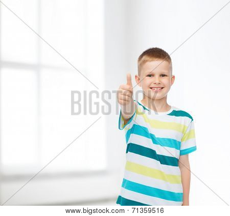 happiness, childhood and people concept - smiling little boy in casual clothes with crossed arms over white room background