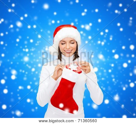christmas, winter, happiness, holidays and people concept - smiling woman in santa helper hat with small gift box and stocking over blue snowy background