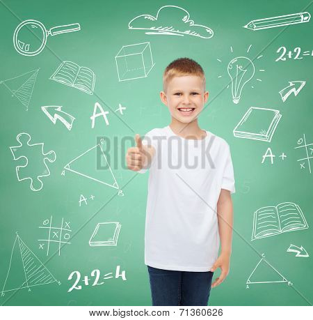 childhood, gesture, education, advertisement and people concept - smiling boy in white t-shirt showing thumbs up over green board with doodles background