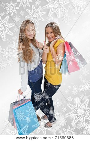 Two beautiful young women with shopping bags the thumbup against snowflakes on silver