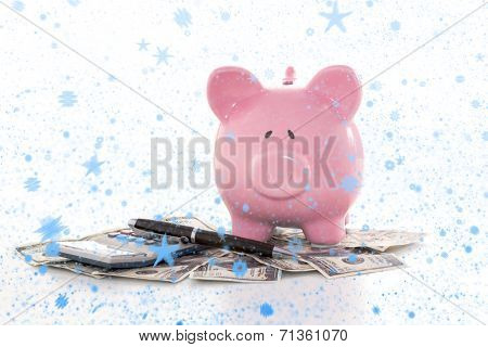 Snow falling against pink piggy bank beside calculator and fountain pen