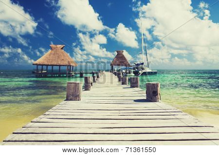 vacation, travel and sea concept - wooden pier with blue water around