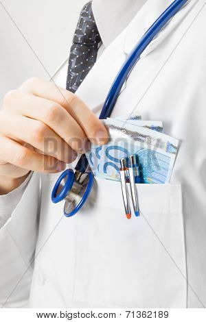Doctor Putting Euro Into His Pocket - Studio Shoot