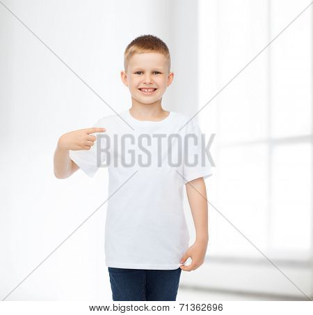 advertising, people, gesture and childhood concept - smiling boy in white blank t-shirt pointing fingers himself over white room background