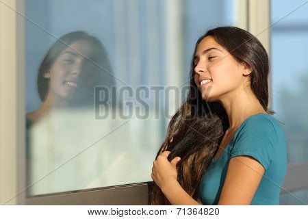 Flirty Teen Girl Combing Her Hair Using A Window Like A Mirror