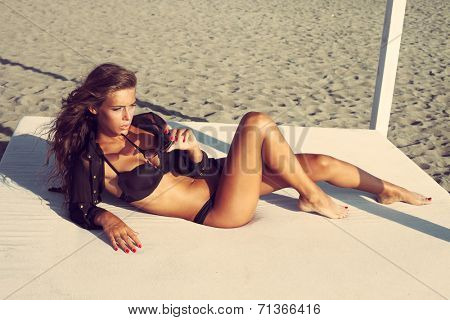 beautiful woman posing on sandy beach in black bikini and shirt lie on white beach bed full body shot