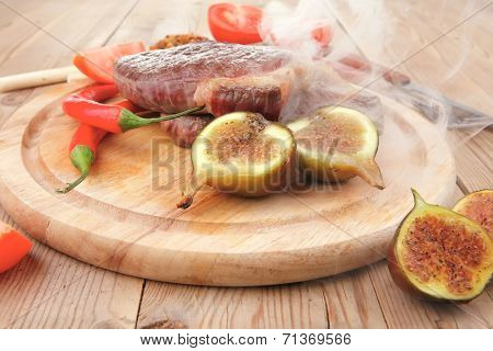 meat entree : grilled beef steak served with red hot cayenne peppers green stuff sweet figs and cutlery on wood plate over wooden table