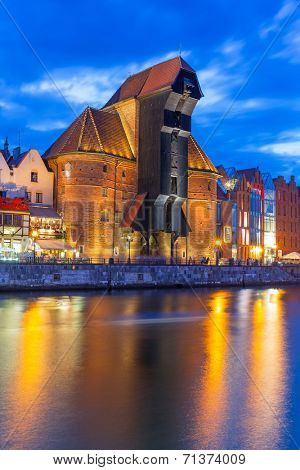 GDANSK, POLAND - 25 JULY 2014: Medieval port crane over Motlawa river at night. This port crane built between 1442 and 1444 is the symbol of Gdansk and the oldest surviving port crane in Europe.