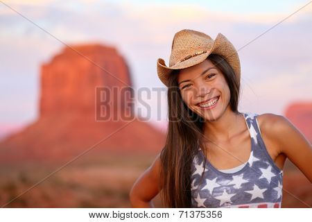 Cowgirl woman happy portrait in Monument Valley wearing cowboy hat. Beautiful smiling multiracial young woman outdoors, Arizona Utah, USA.