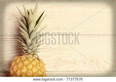 High angle view of a fresh picked pineapple laying on its side on a rustic white wood table. Horizontal format with an instagram look with vignette.