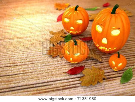 Halloween pumpkins, wooden background with dry leaves