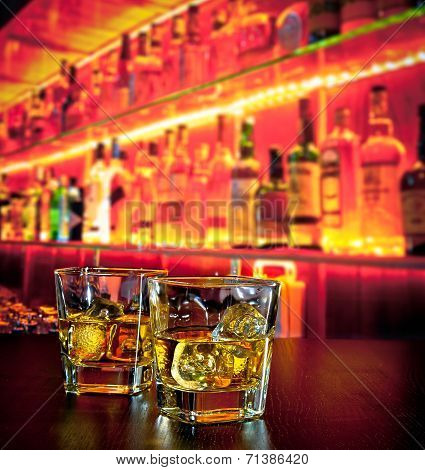Glasses Of Whiskey With Ice On Bar Table Near Whiskey Bottle On Warm Atmosphere