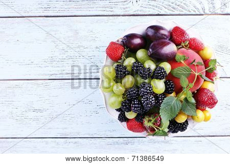 Different berries and fruits in plate on wooden table close-up