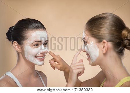 Two beautiful girls applying facial cream mask