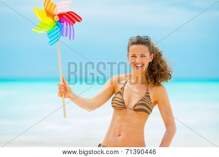 Portrait Of Smiling Young Woman Holding Colorful Windmill Toy