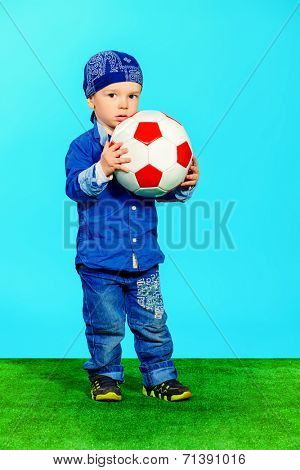 Adorable little boy in jeans clothes standing on a grass with a ball. Fashion. Childhood.