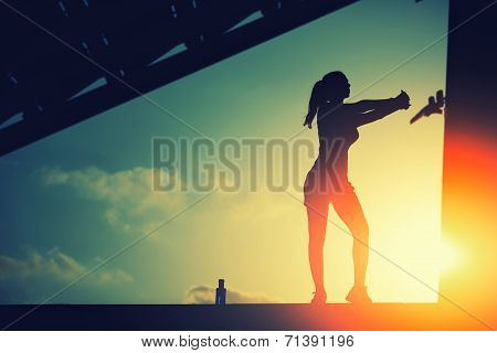 Athletic female jogger silhouette against the sunset doing workout