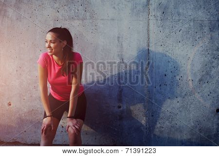 Female jogger in bright sportswear smiling looking away