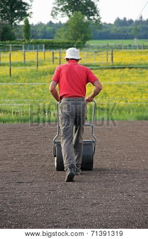 Man Flattening The Soil For Preparing Garden Lawn