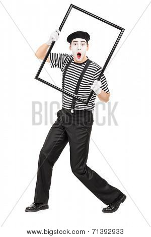 Full length portrait of a mime artist holding a big picture frame isolated on white background