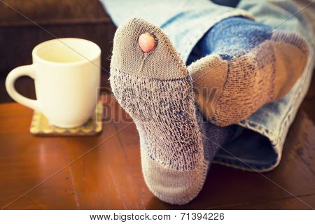 Feet propped up on a coffee table  with a pair of worn out socks with a hole and a toe sticking out of them.