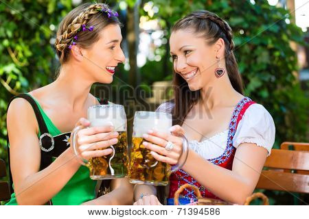 In Beer garden �¢?? female friends in Tracht, Dirndl and Lederhosen drinking a fresh beer in Bavaria, Germany