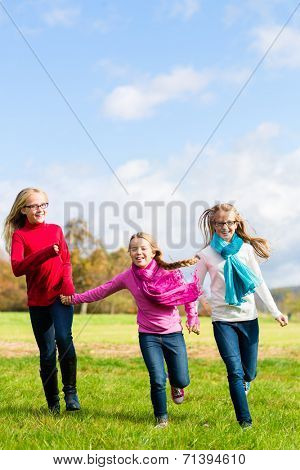 Girls having fun running through fall or autumn park