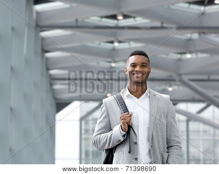 African American Man Smiling With Bag At Airport