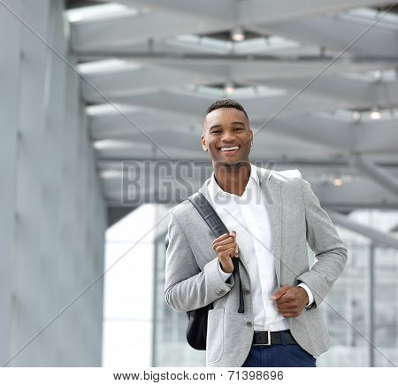 Cheerful Young Man Walking At Airport With Bag