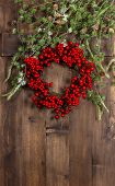pic of christmas wreath  - green christmas tree branches and wreath from red berries over rustic wooden background. festive decoration
