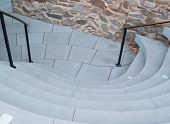 pic of bannister  - This curvy stairwell leads the traveler to pavers against a rustic stone wall - JPG