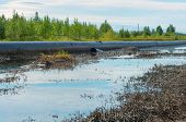 stock photo of pipeline  - Spilled oil around the oil pipeline - JPG