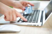 stock photo of holding money  - Hands holding a credit card and using laptop computer for online shopping - JPG