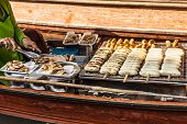 stock photo of peddlers  - Hawkers selling fruits and vegetables in the traditional floating market in Damnoen Saduak near Bangkok Thailand - JPG