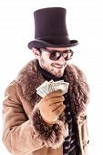 stock photo of hustler  - a young man wearing a sheepskin coat and a top hat isolated over a white background holding banknotes