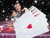 picture of gambler  - Gambler holding whiskey at poker table with digital hand of cards in foreground against snow - JPG