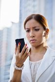 stock photo of disappointed  - Businesswoman with disappointed expression using mobile phone in city street receiving bad news via email - JPG