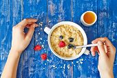 stock photo of porridge  - Top view showing hands eating porridge with berries and honey on a blue wooden table - JPG