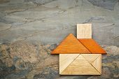 pic of tangram  - abstract picture of a house built from seven tangram wooden pieces against slate rock background - JPG
