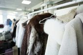 picture of outerwear  - Clean clothes hanging on hangers at dry cleaner - JPG